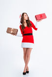 Thoughtful woman in santa claus cloth holding two gift boxes Stock Images