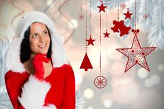 Thoughtful woman in santa costume against digitally generated background Stock Photos