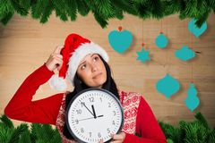 Thoughtful woman in santa hat holding clock Stock Photo