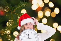 Thoughtful woman in santa hat holding a clock Royalty Free Stock Image