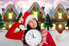 Thoughtful woman in santa hat holding clock Royalty Free Stock Images