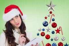 Thoughtful woman in santa hat holding a notepad Royalty Free Stock Image
