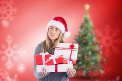 Thoughtful woman in santa hat holding stack of gifts Royalty Free Stock Images