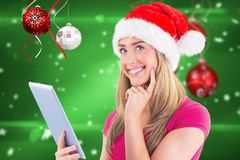 Thoughtful woman in Santa hat using tablet Royalty Free Stock Images
