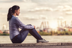 Thoughtful Woman Sits on Bench Facing at the River Stock Photos