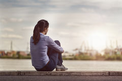 Thoughtful Woman Sits On Bench Facing At The River Royalty Free Stock Photography