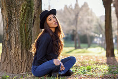 Thoughtful woman sitting alone outdoors wearing hat Stock Photos