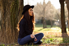 Thoughtful woman sitting alone outdoors wearing hat Stock Images