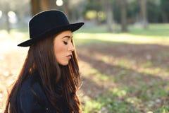Thoughtful woman sitting alone outdoors wearing hat Stock Photo
