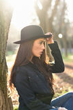 Thoughtful woman sitting alone outdoors wearing hat Stock Photography