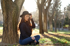 Thoughtful woman sitting alone outdoors wearing hat Royalty Free Stock Photo