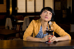 Thoughtful woman sitting at the bar. Thoughtful woman sitting drinking red wine at the bar staring up into the air as she reminisces or daydreams royalty free stock photography