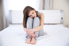 Thoughtful woman sitting on the bed Royalty Free Stock Images