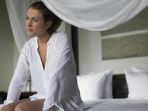 Thoughtful Woman Sitting on Bed Stock Images