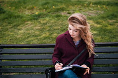 Thoughtful woman sitting on bench and writing in notebook outdoors Stock Photos