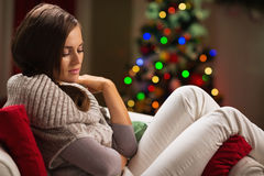 Thoughtful woman sitting on chair in front of tree Royalty Free Stock Photo