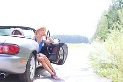 Thoughtful woman sitting in convertible on country road against clear sky Royalty Free Stock Photo