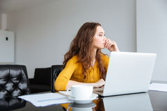 Thoughtful woman sitting at the desk Royalty Free Stock Photo