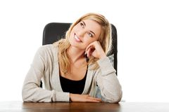 Thoughtful woman sitting at the desk touching chin.  Royalty Free Stock Photo