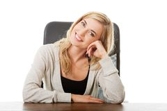 Thoughtful woman sitting at the desk touching chin Royalty Free Stock Photo