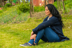 Thoughtful woman. Sitting on grass in garden Royalty Free Stock Image