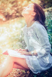 Thoughtful Woman Sitting on Grasses at the Garden stock photography