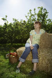 Thoughtful Woman Sitting On Hay Bales Near Orchard Royalty Free Stock Images