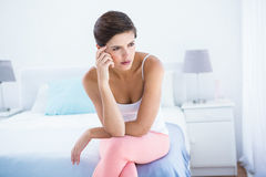 Thoughtful woman sitting on her bed Royalty Free Stock Photos