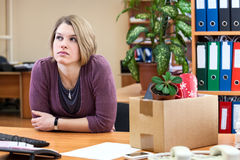 Thoughtful woman sitting in the office with the collected things Royalty Free Stock Photography