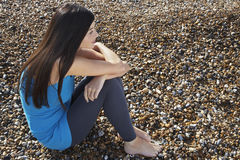 Thoughtful Woman Sitting On Pebbles At Beach Stock Photography