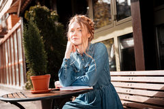 Thoughtful woman sitting and reading a book in outdoor cafe Royalty Free Stock Photo