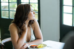 Thoughtful woman sitting at restaurant table Royalty Free Stock Photo
