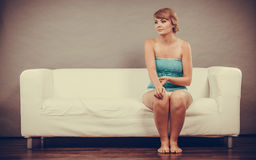 Thoughtful  woman sitting on sofa Royalty Free Stock Images