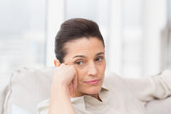Thoughtful woman sitting on sofa Stock Image