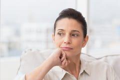 Thoughtful woman sitting on sofa Stock Photography