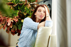Thoughtful woman sitting on the sofa Stock Images