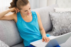 Thoughtful woman sitting on sofa and using laptop Stock Image