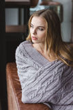 Thoughtful woman sitting on sofa wrapped in grey knitted coverlet Royalty Free Stock Photo