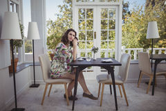 Thoughtful woman sitting at table Royalty Free Stock Images