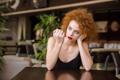 Thoughtful woman sitting at the table in restaurant Royalty Free Stock Image