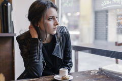 Thoughtful Woman Sitting at the Table with Snacks Stock Images