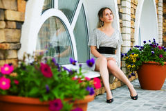 Thoughtful woman sitting on the window. Royalty Free Stock Photography