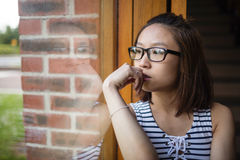 Thoughtful woman sitting on windowsill Stock Photo