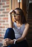 Thoughtful woman sitting on windowsill Royalty Free Stock Photo