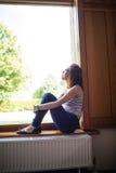 Thoughtful woman sitting on windowsill Royalty Free Stock Image