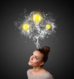 Thoughtful woman with smoke and lightbulbs above her head Stock Photo