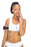 Thoughtful woman in sportswear listening to music Stock Photo