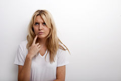 Thoughtful woman standing against white background Stock Photo