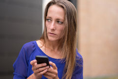 Thoughtful woman standing holding her mobile Royalty Free Stock Images