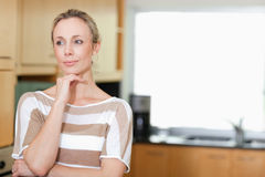Thoughtful woman standing in kitchen Royalty Free Stock Photos